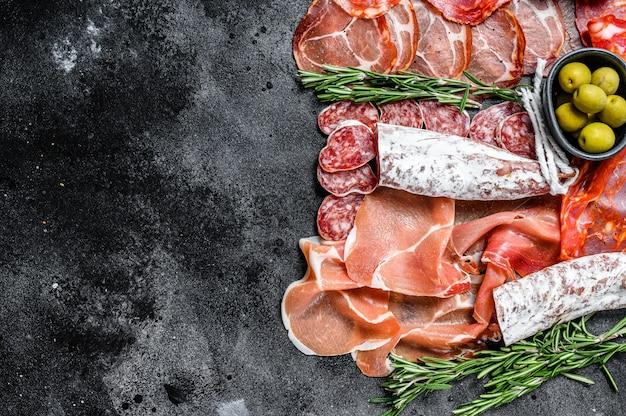 Plateau de viande séchée de tapas espagnoles traditionnelles. chorizo, serrano, lomo et fuet. fond noir. vue de dessus. espace copie