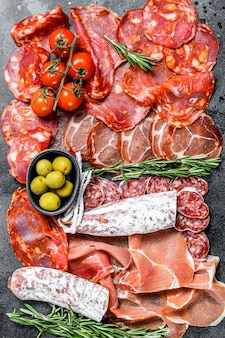 Plateau de viande séchée de tapas espagnoles traditionnelles. chorizo, serrano, lomo et fuet. surface noire. vue de dessus.