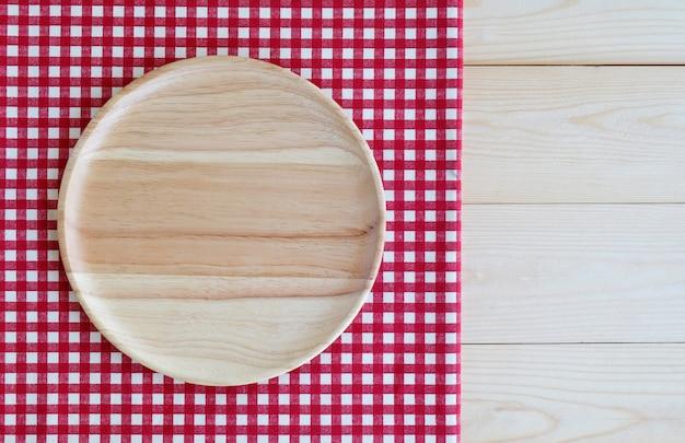 Plateau vide en bois rond sur une nappe blanche rouge qui couvre le fond de la table en bois
