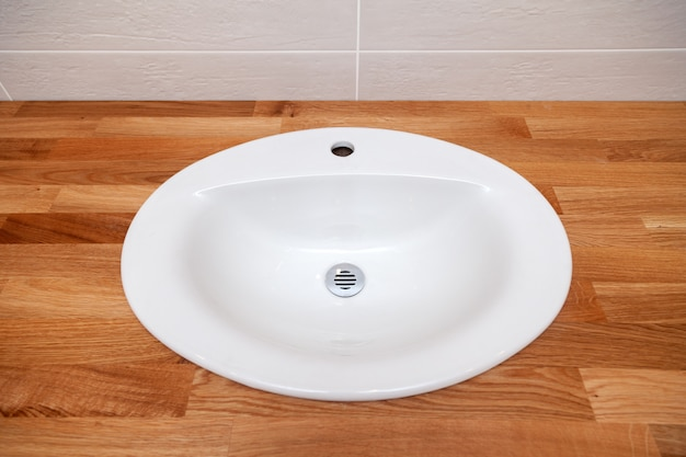 Plateau vide en bois teck brun closeup avec évier en céramique rond blanc. réparation, rénovation de salle de bain dans des appartements, hôtel, spa, installation de plomberie, robinet
