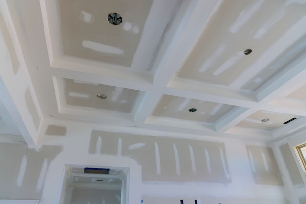 Plâtrage des joints de gypse sur les murs et le plafond d'une nouvelle maison en cours de processus