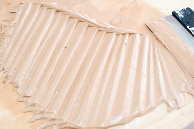Plâtre fluide rose. application à la truelle sur un mur de béton. mastic pour la décoration murale. réparation de conception