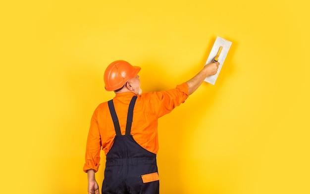 Plâtrier dans le mur de plâtrage uniforme de travail à l'intérieur. homme avec une spatule. processus d'application d'une couche de mastic. outils de plâtrage pour plâtre. spatule à plâtre sur plaque de plâtre jaune.