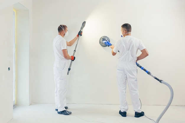 Le plâtrier lisse la surface du mur avec une machine murale avec du papier de verre.