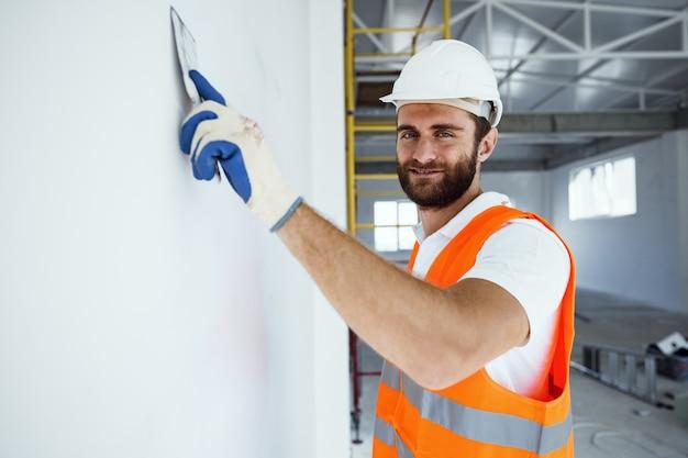 Plâtrier en vêtements de travail lissant la surface du mur du bâtiment à l'intérieur