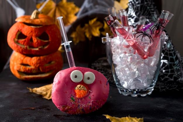 Plats avec des beignes glacés, avec un cocktail rouge dans un tube de verre dans un seau de glace