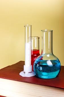 Les plats chimiques et les tubes à essai sont sur un livre épais. recherche en laboratoire. photo de haute qualité