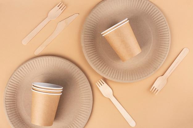 Plats écologiques sur fond beige, assiettes et verres en papier, fourchettes et fourchettes en bois, vue de dessus