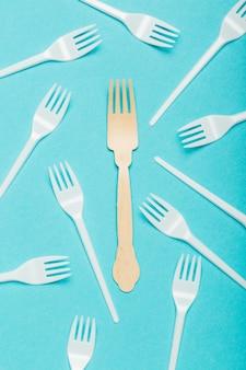 Plats écologiques, fourchettes en bois et en plastique sur fond bleu