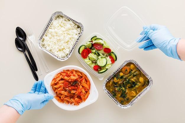 Plats à emporter dans des aliments contaitakeaway jetables dans des récipients jetables riz, curry de légumes, pâtes italiennes à la sauce tomate et salade fraîche et saine. et les mains dans des gants chirurgicaux médicaux.