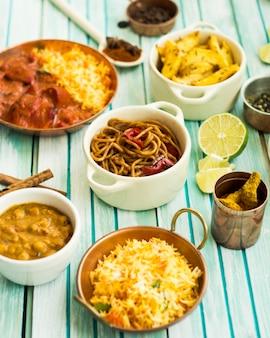 Plats et épices autour du pot avec des pâtes et du citron vert