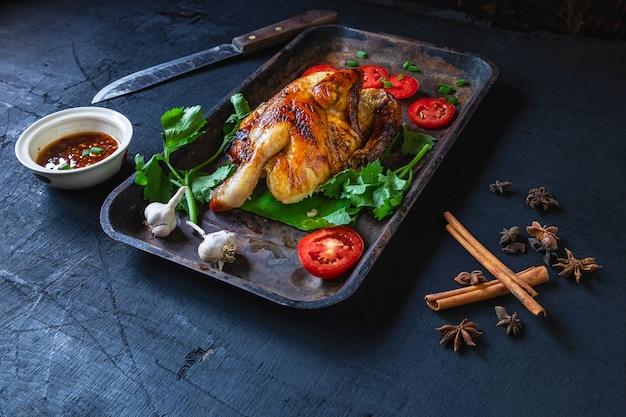 Plats de poulet grillé et sauce trempette du four sur un fond noir