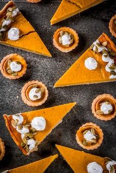 Plats traditionnels d'automne. halloween, thanksgiving. ensemble de tarte à la citrouille épicée et tartelettes à la citrouille avec crème fouettée et graines de citrouille sur une table en pierre noire. vue de dessus