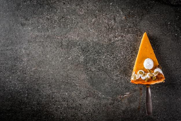 Plats traditionnels d'automne. halloween, thanksgiving. un morceau de tarte à la citrouille épicée avec de la crème fouettée et des graines de citrouille sur une table en pierre noire. copier la vue de dessus de l'espace