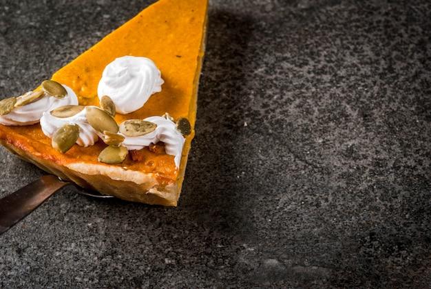 Plats traditionnels d'automne. halloween, thanksgiving. un morceau de tarte à la citrouille épicée avec de la crème fouettée et des graines de citrouille sur une table en pierre noire. fond