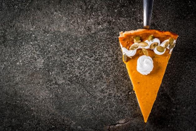 Plats traditionnels d'automne. halloween, thanksgiving. un morceau de tarte à la citrouille épicée avec de la crème fouettée et des graines de citrouille sur une table en pierre noire. vue de dessus du fond