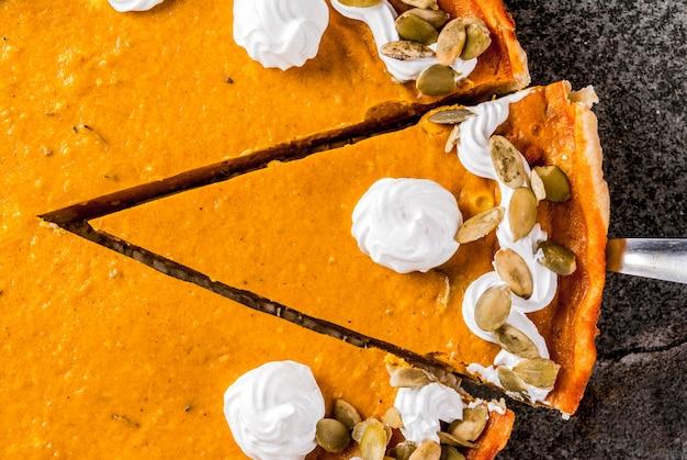 Plats traditionnels d'automne. halloween, thanksgiving. tarte à la citrouille épicée en tranches avec crème fouettée et graines de citrouille sur une table en pierre noire. espace de copie vue de dessus