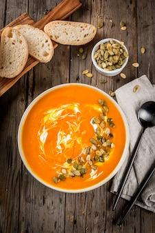 Plats traditionnels d'automne et d'hiver, soupe de citrouille chaude et épicée avec des graines de citrouille, de la crème et de la baguette fraîchement cuite, sur une vieille table en bois rustique, vue de dessus