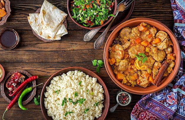 Plats traditionnels de tajine, couscous et salade fraîche sur une table en bois rustique. tajine de viande d'agneau et de citrouille. vue de dessus. mise à plat