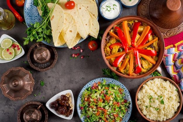Plats traditionnels de tajine, couscous et salade fraîche sur une table en bois rustique.