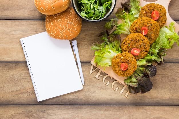 Plats végétaliens plats à côté de la maquette du cahier