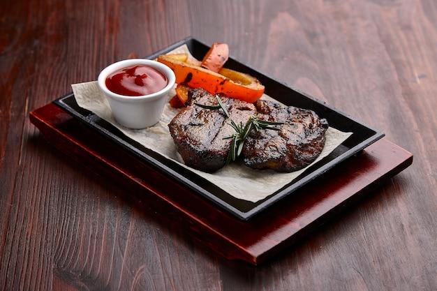 Plats de viande grillée appétissants avec sauce sur une table en bois sombre.