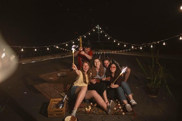 Plein d'amis heureux avec des feux d'artifice