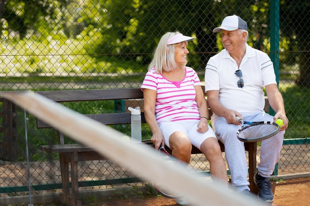 Plein d'amis seniors assis sur un banc