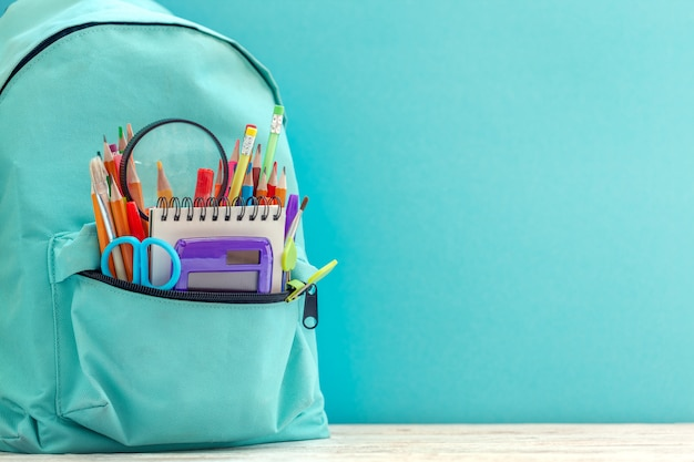 Plein bleu école sac à dos avec des fournitures différentes sur fond bleu.