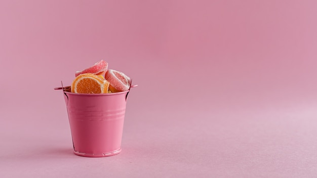 Plein de bonbons de gelée de fruits colorés dans un seau rose