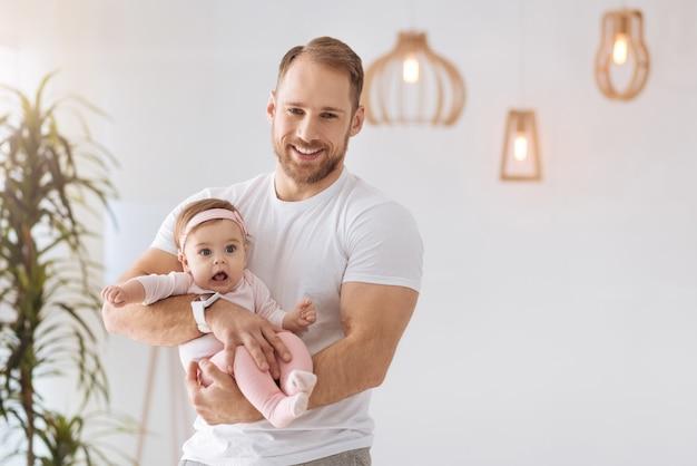 Plein de bonheur. athlétique jeune père positif debout à la maison et tenant son nouveau-né tout en exprimant son amour et ses soins