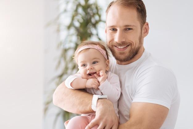 Plein de bonheur. joyeuse petite fille souriante ludique couchée dans les mains du jeune père et regardant ailleurs tout en exprimant le bonheur
