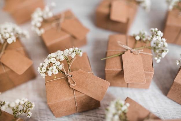 Plein cadre de boîtes en carton avec étiquette et fleurs d'haleine de bébé sur fond en bois