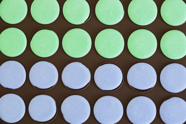 Plein cadre du mélange de macarons verts et violets dans la plaque de cuisson noire
