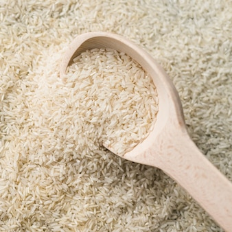 Plein cadre de riz blanc non cuit avec une cuillère en bois