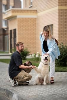 Plein coup couple caresser le chien à l'extérieur