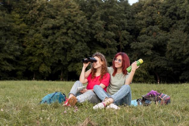 Plein coup de femmes avec des jumelles debout sur l'herbe