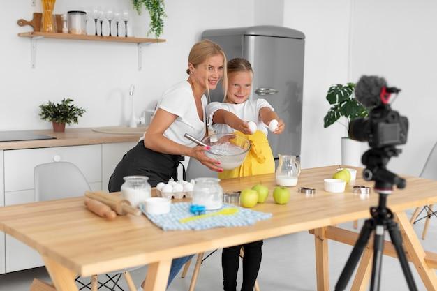 Plein coup fille souriante et femme cuisinant