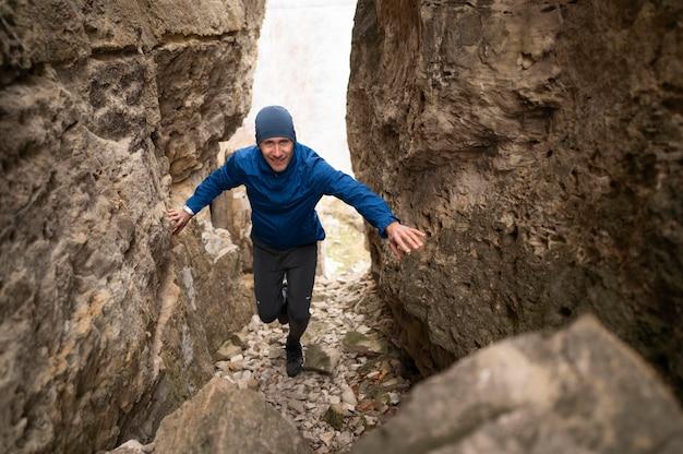 Plein coup jeune homme marchant à travers les rochers