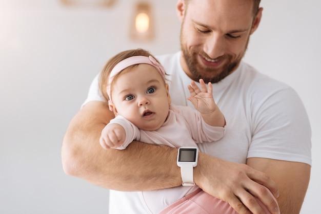 Plein de curiosité. beau bébé assez impliqué se trouvant dans les mains du jeune père et regardant ailleurs tout en exprimant son intérêt et sa positivité