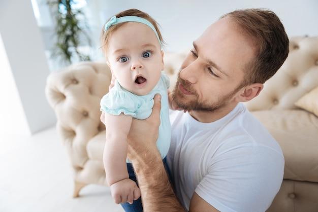 Plein d'émotions heureuses. drôle mignon enfant en bas âge agréable debout près de son jeune père et regardant ailleurs tout en exprimant son intérêt et sa positivité