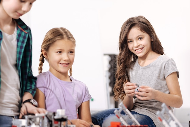 Plein d'émotions positives. mignons jolis enfants optimistes assis dans le laboratoire de robotique et testant des appareils électroniques tout en ayant une leçon de sciences