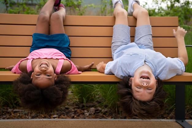 Plein d'enfants allongés sur un banc