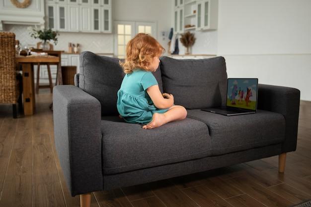 Plein d'enfants assis sur un canapé avec un ordinateur portable