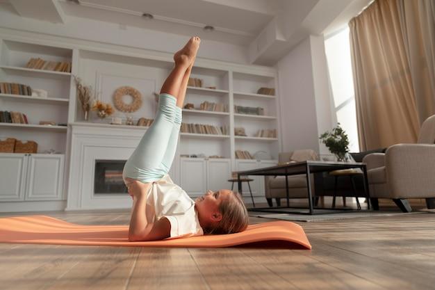 Plein d'enfants faisant du yoga