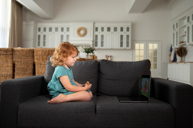 Plein d'enfants mignons assis sur un canapé avec un ordinateur portable