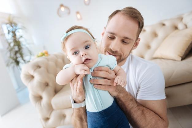 Plein d'intérêt. curieuse belle fille positive debout près de son jeune père et regardant ailleurs tout en exprimant son intérêt et en faisant des pas