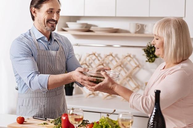 Plein de positivité. heureux homme barbu positif debout dans la cuisine et profiter du week-end tout en cuisinant une salade avec sa mère senior