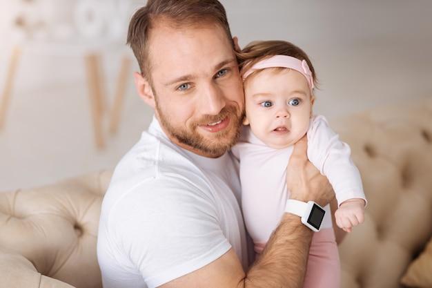 Plein de positivité. heureux jeune père souriant assis sur le canapé à la maison et étreignant son enfant tout en exprimant ses soins et son amour