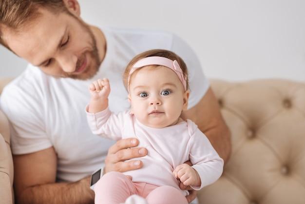 Plein de soins. heureux homme impliqué positif assis sur le canapé à la maison et étreignant son enfant tout en exprimant des émotions tendres et au repos